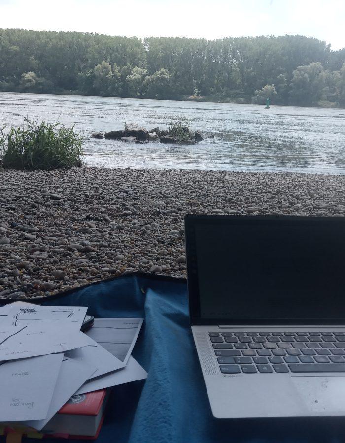 Laptop, Postkarten auf Schotterbank neben der Donau